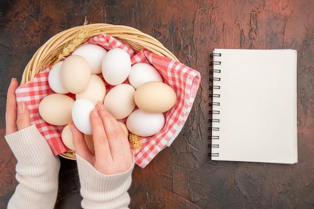 Vista dall'alto uova di gallina bianche all'interno del cesto con un asciugamano sul tavolo scuro cibo animale crudo fattoria foto a colori pasto