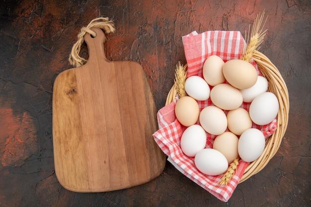 Vista dall'alto uova di gallina bianca all'interno del cesto con asciugamano sul tavolo scuro