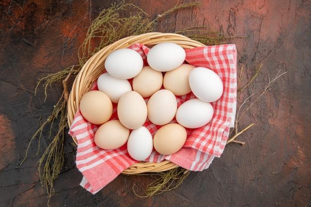暗いテーブルの上のタオルとバスケットの中の白い鶏卵の上面図写真動物の食事食品生の農場の色