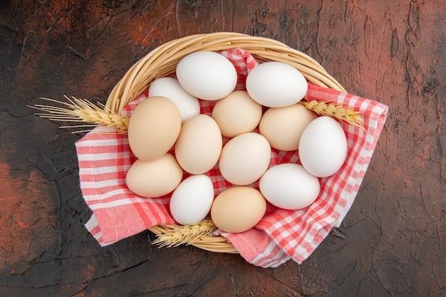 暗いテーブルの上のタオルとバスケットの中の白い鶏卵の上面図