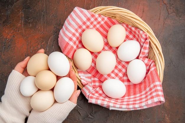 暗いテーブルの上の女性の手の中に白い鶏卵の上面図