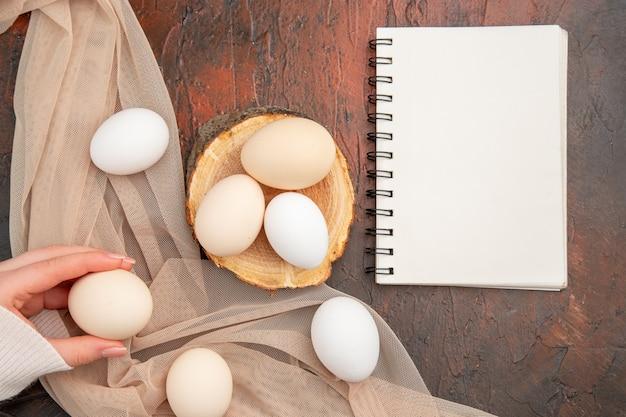 暗いテーブルの上の白い鶏の卵の上面図食事動物生写真農場の食べ物朝食の色