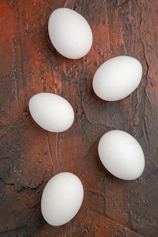 暗いテーブルの上の白い鶏の卵の上面図動物の食事食品農場のカラー写真
