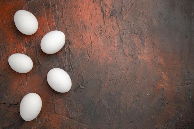 暗いテーブルの動物の食事の食糧農場の上面図白い鶏の卵