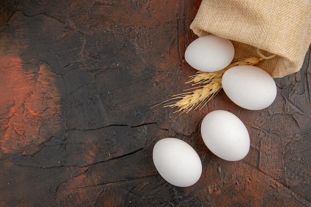 暗いテーブルの動物の食事の上面図白い鶏卵