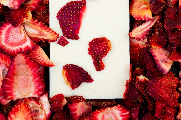 Top view of a white chocolate bar on dried strawberry slices background