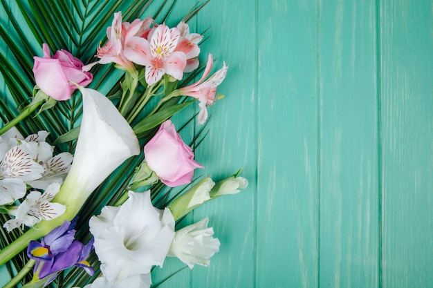 Top view of white color calla lilies and gladiolus with dark purple iris and pink roses and alstroemeria flowers on palm leaf on green wooden background with copy space