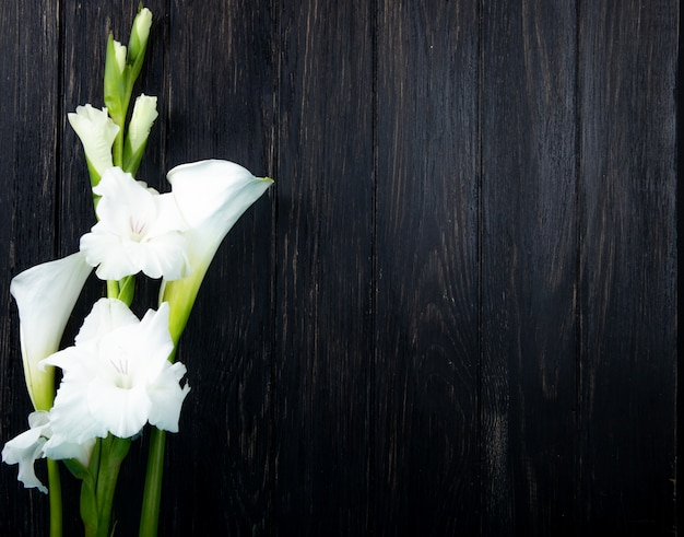 Top view of white color gladiolus and calla lily flowers isolated on black background with copy space
