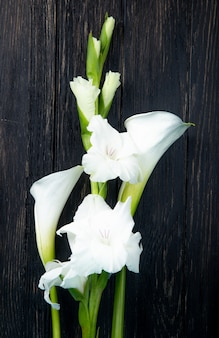 Vista superiore dei fiori bianchi di gladiolo e della calla di colore isolati su fondo nero