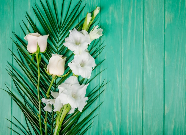 Top view of white color roses and gladiolus flowers on palm leaf on green wooden background with copy space