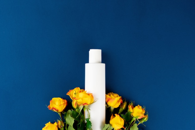 Top view of white cosmetic container with flowers on blue background, copy space