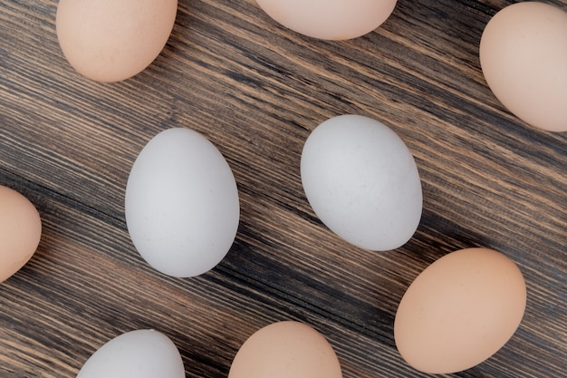 Top view of white and cream colored chicken eggs isolated on a wooden background