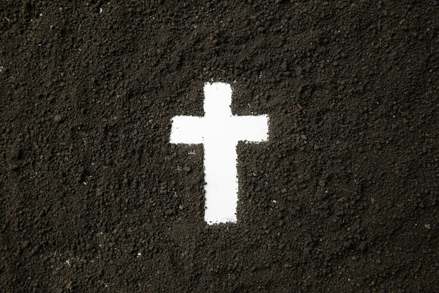 Top view of white cross shape with dark soil