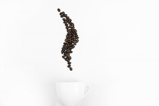 The top view of the white cup with coffee beans in the form of steam on the white blackground.