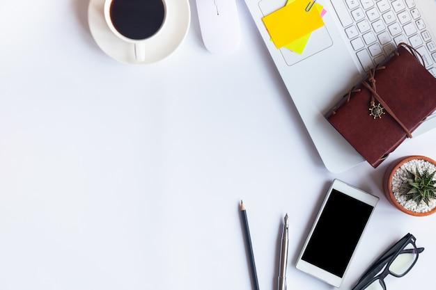 トップビューホワイトデスクオフィス。フラットにテーブルの重要な要素のワークスペースを置きます。