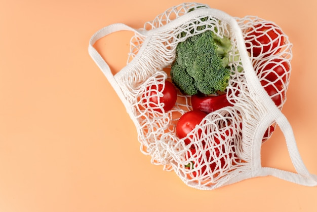 Top view of white eco net bag with vegetables