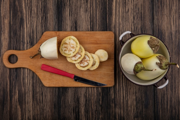 まな板にナイフと木製の背景に鍋で白いナスのスライスの上面図