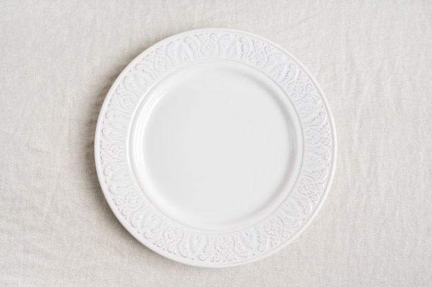 Top view of the white empty ceramic plate on linen tablecloth with copy space.  concept food table serving.