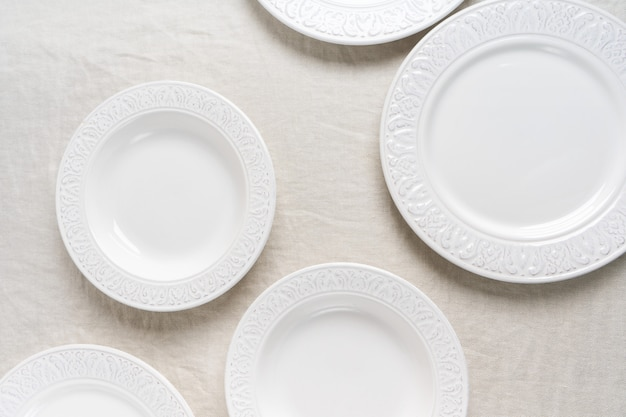 Top view of the white empty ceramic plates on linen tablecloth with copy space. preparation to the table setting.  concept food table serving.