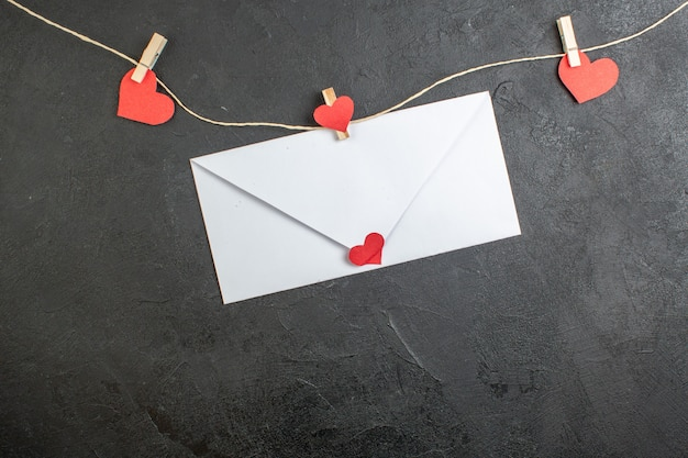 어두운 배경에 메모가 있는 상위 뷰 흰색 봉투 사랑 커플은 결혼 선물 심장 색상을 느끼고 있습니다.