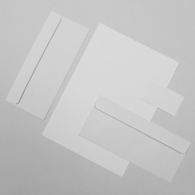 Вид сверху белые конверты и бумага