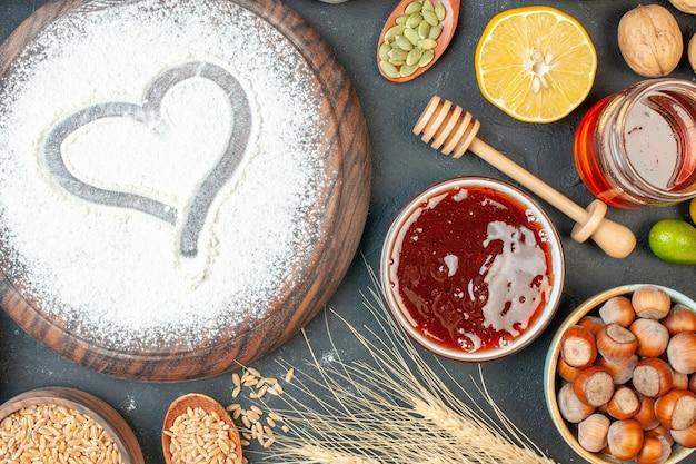 Vista dall'alto farina bianca a forma di cuore con noci su frutta scura torta dolce tè dessert biscotto torta pasta di zucchero