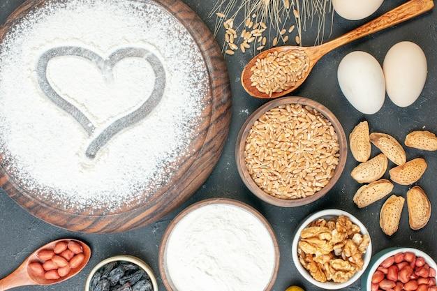 灰色のケーキフルーツ甘いパイ茶デザートビスケット砂糖ペストリーにナッツとハート形の白い小麦粉の上面図