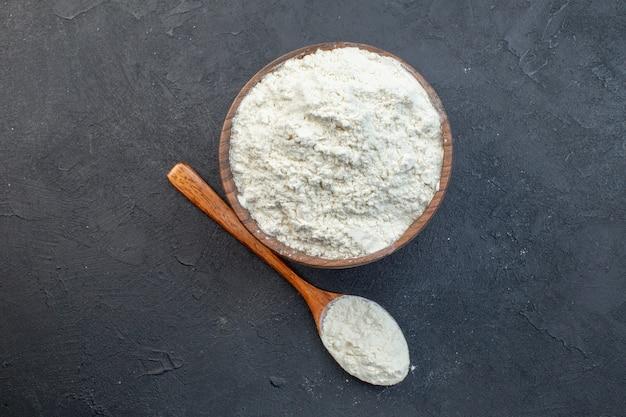 Вид сверху белая мука внутри тарелки на темном фоне тесто испечь торт пирог бисквитная пыль