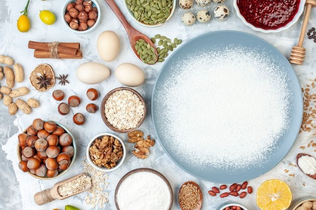 Vista dall'alto farina bianca all'interno del piatto con semi di noci e uova su pasta bianca cuocere la gelatina di noci colorante alimentare