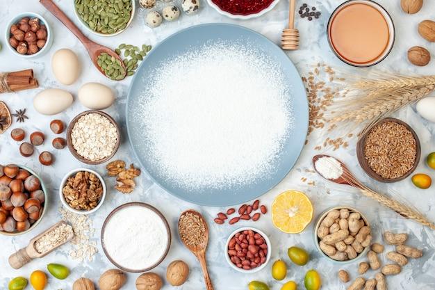 Vista dall'alto farina bianca all'interno del piatto con semi di noci e uova su pasta bianca cuocere la gelatina di noci per foto a colori alimentari