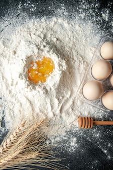 Vista dall'alto farina bianca mescolata con uovo su sfondo scuro lavoro di pasticceria torta di uova da forno cucina del lavoratore
