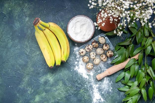 上面図ダークブルーの背景にバナナと卵と白い小麦粉生地食品ペストリーオーブンケーキパイダストベイク