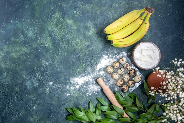 Top view white flour with bananas and eggs on a dark blue background dough food pastry oven cake pie dust bake