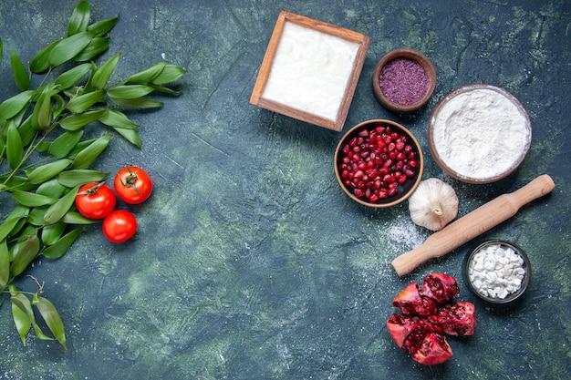 Vista dall'alto farina bianca con melograni e pomodori su sfondo blu scuro colore pasta alimentare frutta verde