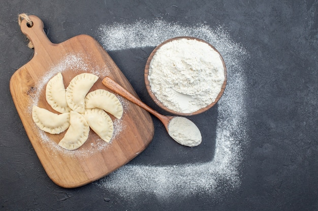 Top view white flour with raw little hotcakes on dark background pie dough oven cake bake cooking dust oil