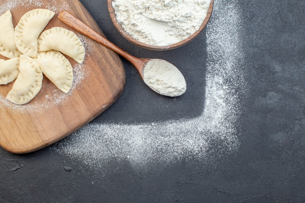 Top view white flour with raw little hotcakes on dark background pie dough oven cake biscuit bake cooking oil