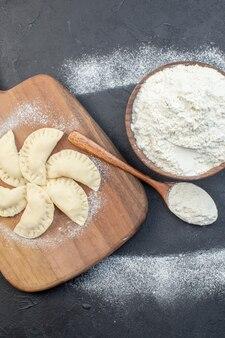 어두운 배경 파이 반죽 오븐 케이크 비스킷 베이킹 요리 먼지에 원시 작은 핫케이크와 함께 상위 뷰 흰색 밀가루
