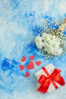 Вид сверху белые цветы маленькие красные сердечки подарок на синем фоне