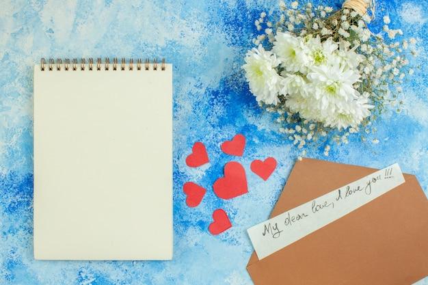 Вид сверху белые цветы блокнот маленькие красные сердечки любовное письмо на синем фоне