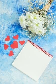 Вид сверху белые цветы блокнот маленькие красные сердечки на синем фоне