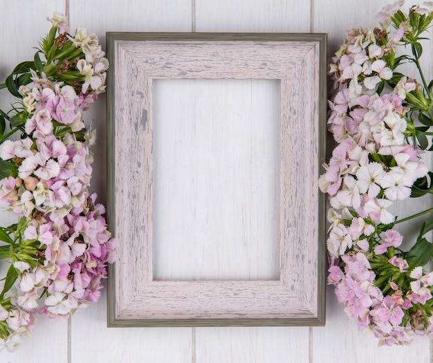 Top view of white frame with flowers on a white surface