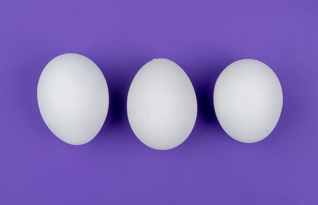 Top view of white fresh chicken eggs arranged in a line on a violet background