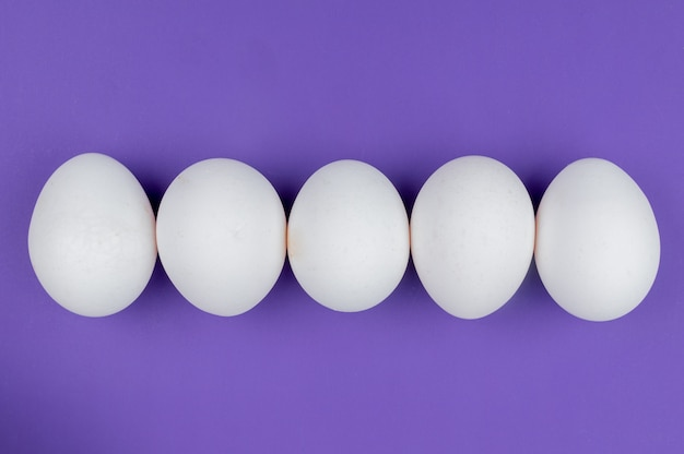 Top view of white fresh and healthy chicken eggs arranged in a line on a violet background