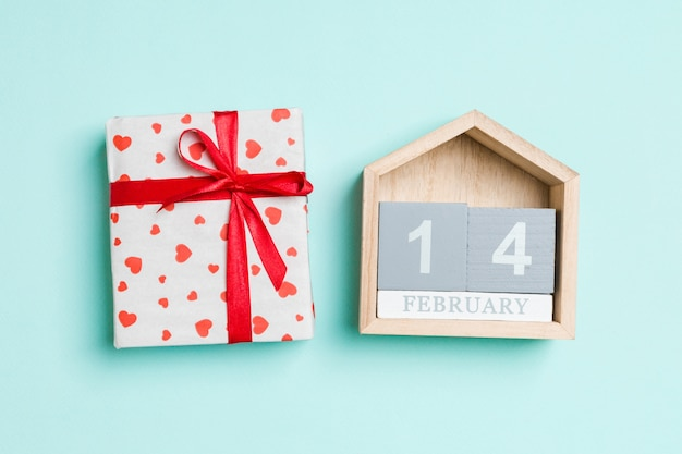 Top view of white gift boxes with hearts and wooden calendar on colorful background. the fourteenth of february. valentine's day concept