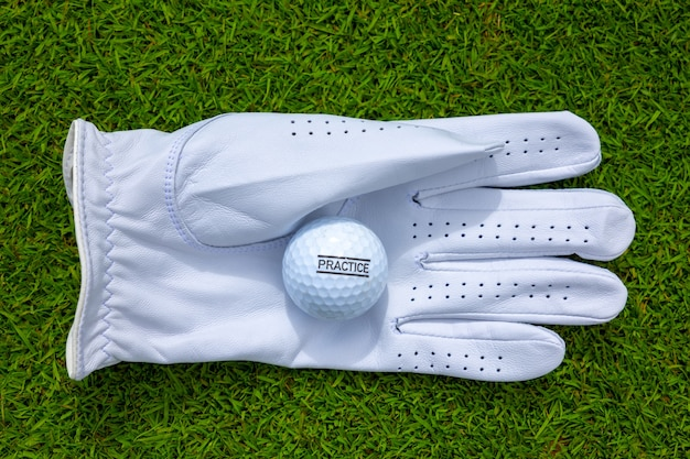 Top view of a white golf glove with a golf ball on a  grassy field