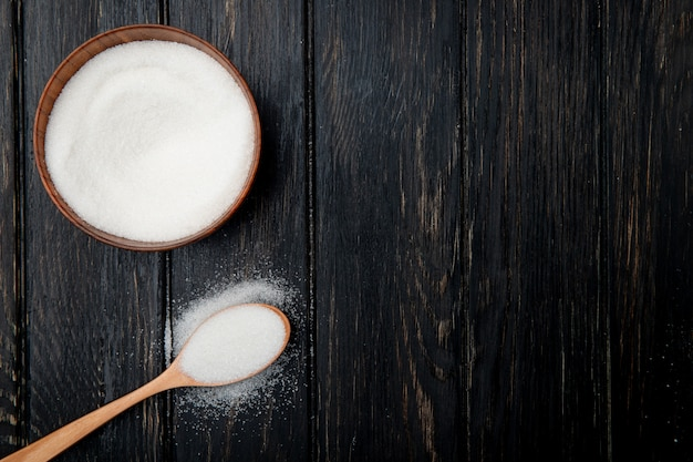Top view of white granulated sugar in a wooden bowl and in a wooden spoon on black rustic background with copy space