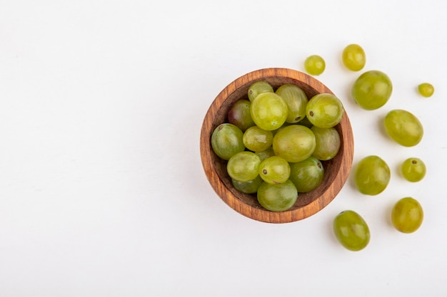 Top view of white grape berries in bowl and on white background with copy space