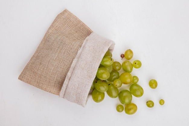 Top view of white grape berries spilling out of sack on white background