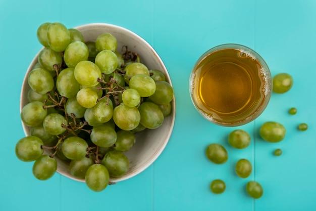 Vista dall'alto di uva bianca nella ciotola e succo d'uva in vetro su sfondo blu