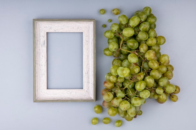 Top view of white grape and frame on gray background with copy space